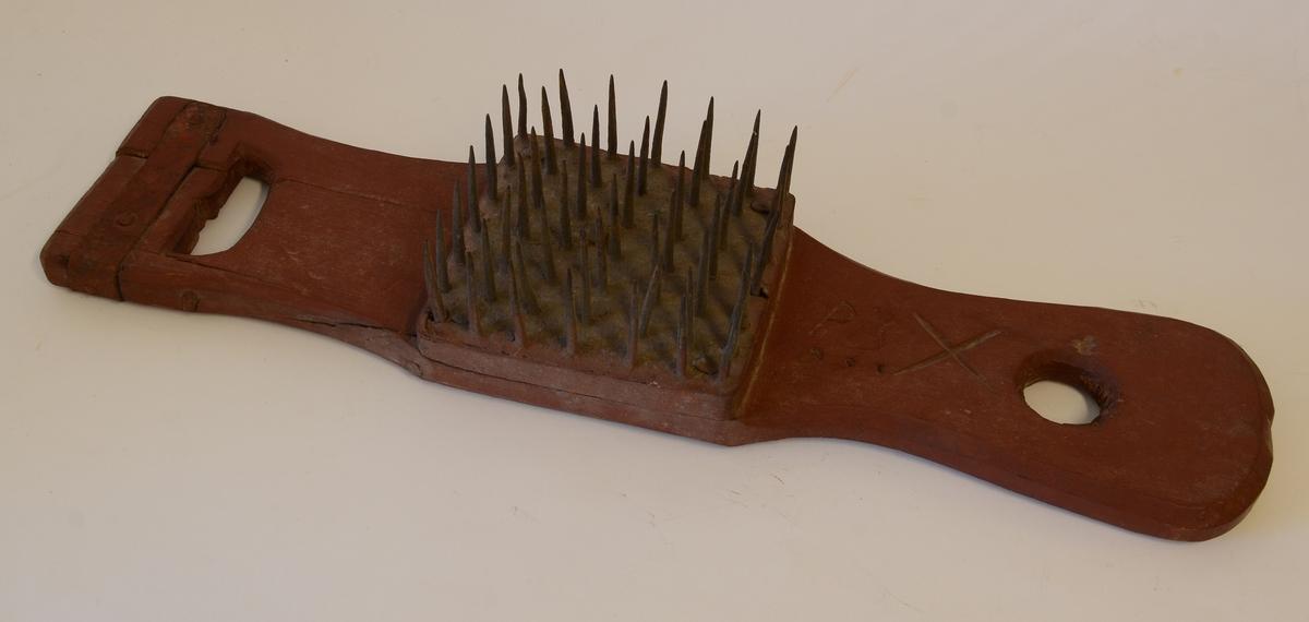 Lin- eller hamphäckla av trä med fyrkantig kam bestående av en fyrkantig träplatta, omdragen av ett järnband. I plattan är kamspikarna fästade. Ett handtag är lagat med ett järnband.