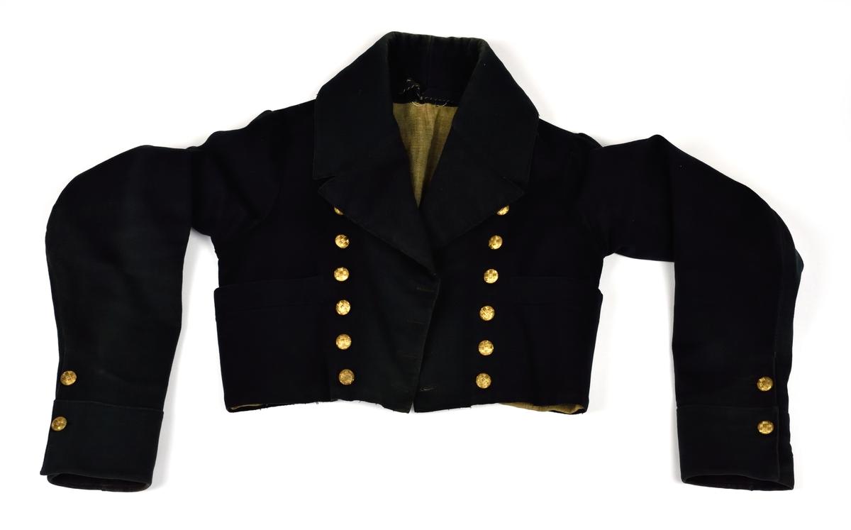 Svart brudgumsjacka med mässingsknappar som är dekorerade med flätmönster. Jackan är dubbelknäppt fram med sex par knappar. Jackan är smyckad med två knappar på vardera ärm samt två i ryggen.