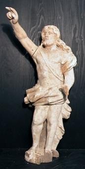 Träskulptur, Johannes döparen eller en Segrande Kristus. Hans högra arm hålls uppsträckt med handen i en segrande gest. Vänster hands fingrar är avbrutna, har hållit om ett attribut. Delar av postament är avbrutna. Manteln i glansförgyllning på röd bolus. Hår och skägg glansförgyllda.
