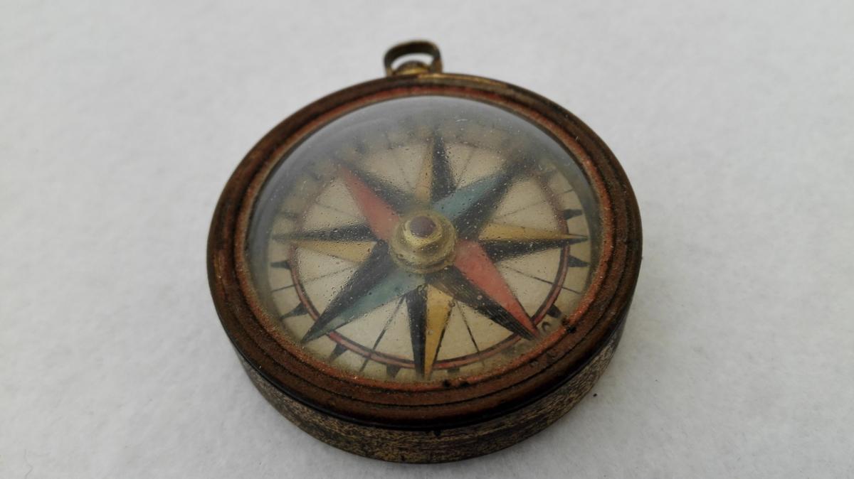 Kompas.  Kompas i messingindfatning, paa oversiden uhrglas. Har hempe som et lommeuhr.  Diameter 4,4 cm. Har tilhørt eidsvoldsmanden, generaladjutant O.E. Holck.  Gave fra datteren fru kaptein Hartvig, Alværen, Lavik.