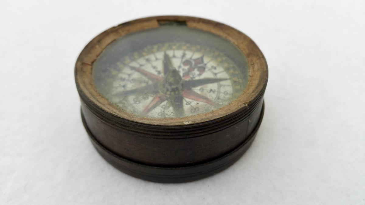 Form: Øskja til kompasset er rund. Kompas.  Kompas i rund messingæske. Til æsken hører skruelaag, over kompasset kidet fast glas, diameter 4,9 cm. Har tilhørt eidsvoldsmanden, generaladjutant O.E. Holck.  Gave fra datteren fru kaptein Hartvig, Alværen, Lavik.