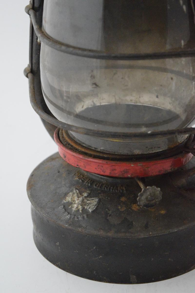 Stormlykt, sylindrisk form med sokkel, ramme og håndtak, også kalt fjøslykt blant annet. Rød ring rett over parafinbeholderen.