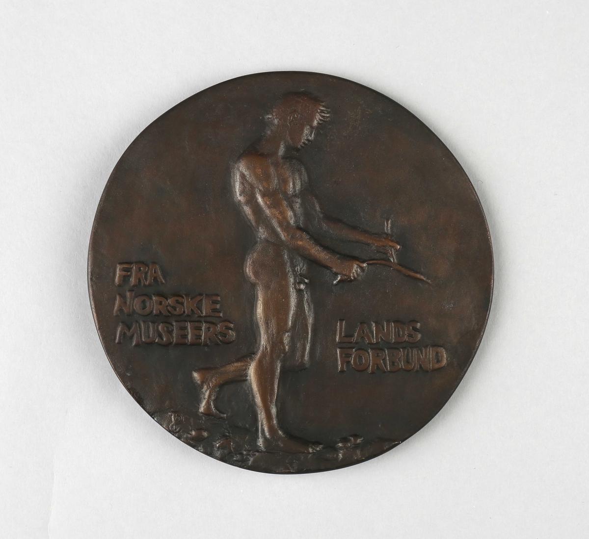 Minneplate med relieff av Hans Aall (forside) og av naken mannsperson med ønskekvist (bakside).