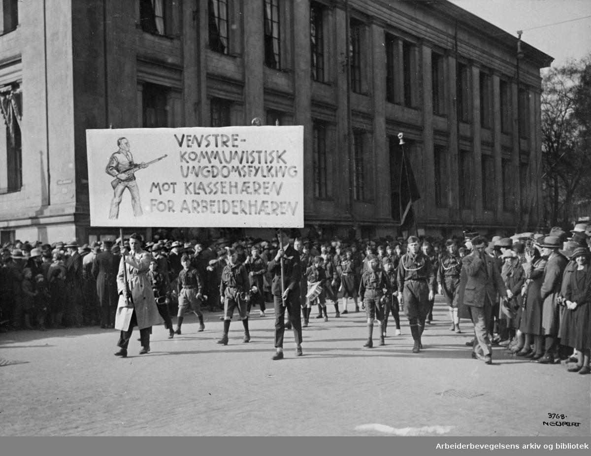 1. mai 1924-1925. Røde speidere i demonstrasjonstoget som svinger inn på Karl Johans gate fra Universitetsgata. .Parole: Venstrekommunistisk ungdomsfylking - Mot klassehæren - For arbeiderhæren.