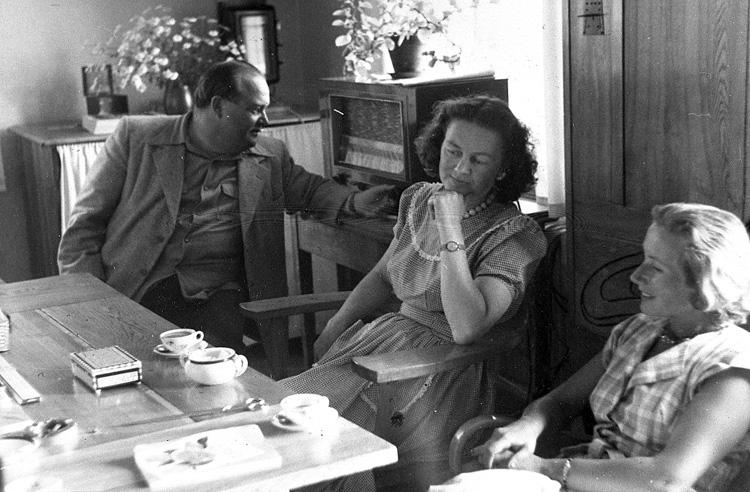 """Enligt uppgift: """"Fotografi från biblioteket ca 1954-1955. Från vänster syns byråchef vid Fiskeristyrelsen Lars Wikland med fru samt fru Nils Jerlov. I bakgrunden syns ett kortskåp (med draperi""""."""