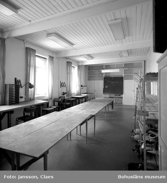 """Enligt uppgift: """"Lektionssal i bottenplan, tidigare kallat för """"trålrummet"""". I rummet fanns fram på 1930-talet hål i golvet för ostronbassänger i källarplan. Under 1930-talet sattes hålen i golven igen. Som """"trålrummet"""" användes rummet för förvaring av trålar, som tillhörde forskningsfartygens utrustning. De väggfasta skåp som syns längst ner i rummet har förmodligen funnits sedan 1930-talet. Mellan ca 1960-1965 gjorde rummet om till lektionssal, mattor lades in, och skåp (längs vänstra väggen) och svart tavlor längs väggarna sattes upp""""."""