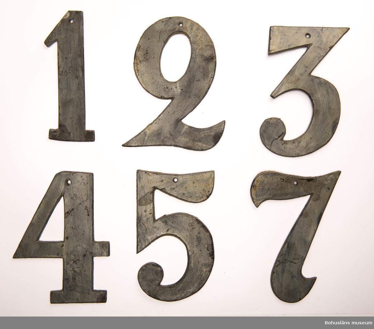 Siffror av blyplåt, etta, tvåa, trea, fyra, femma, sjua, på baksidan märkta b, c, d, e, f, g. Målade. Siffrorna hör till nummertavla UM00405 från Norra Ryrs gamla kyrka,  Ur handskrivna katalogen 1957-1958: Nummertavla 1732 Lane Ryr H, utan stjärnan: 62,5 cm. Br. 39 cm; trä, profil. ramlist, upptill 6-uddig stjärna.  6 tillk. siffror av bly, vitmålade, etta, tvåa, trea, fyra, femma, sjua, nr 405 b - 405 g. Föremålen oskadade.  Lappkatalog: 13