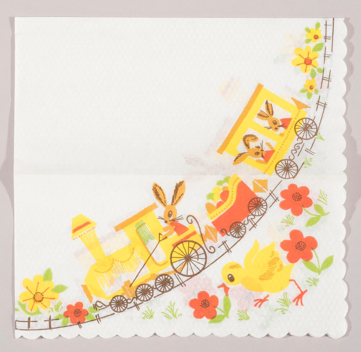 Et tog med lokomotiv og to vogner. En påskeharer sitter i lokomotivet og to i en vogn. I en tredje vogn er der påskeegg. En kylling løper i en blomstereng med røde og gule blomster.