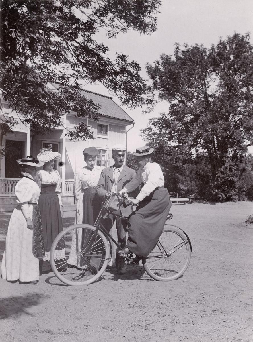 En grupp ungdomar samlade framför Skällviks prästgård Korsnäs. Vid tiden disponerades bostället av kyrkoherde Gustaf Leonard Lundqvist och dennes maka Jauquette. Identifierad på bilden är kvinnan på cykeln, kyrkoherdeparets dotter Amalia Lundqvist. Fotografen är möjligtvis den fotointresserade fadern.