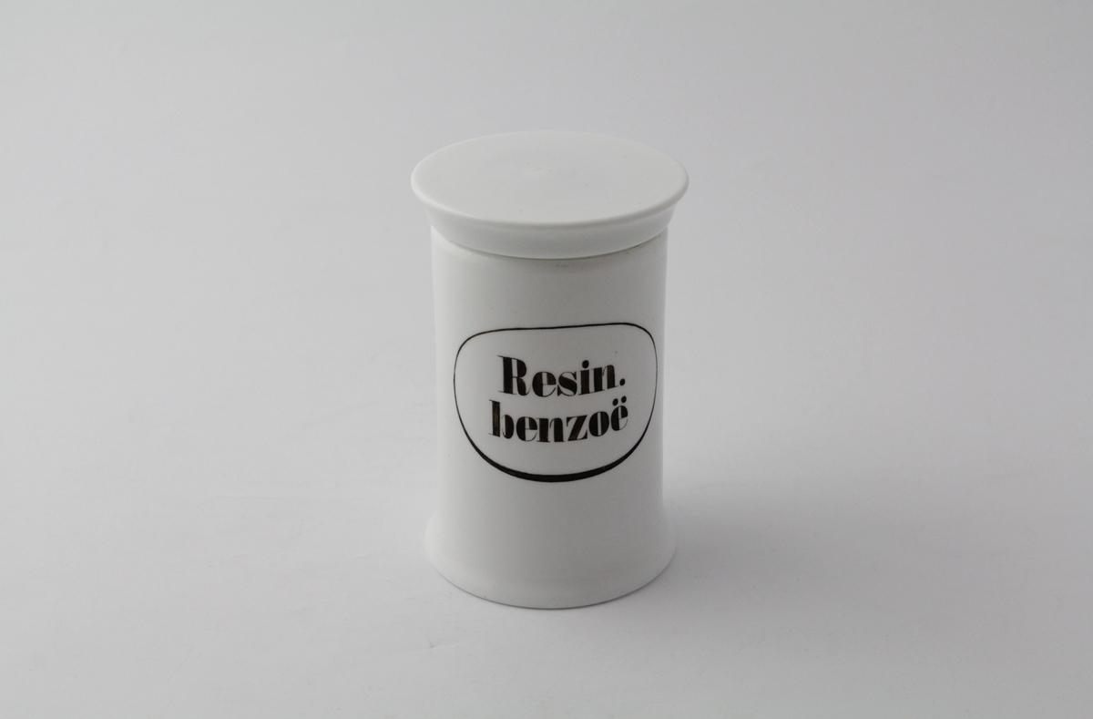 Hvit, sylindrisk porselenskrukke med rundt flatt porselenslokk. Sort påmalt påskrift med oval ring rundt. Brukt til oppbevaring av legemiddelurter med mer på apotek. Har inneholdt benso harpiks som ble brukt i salver med mer til konservering og duft.
