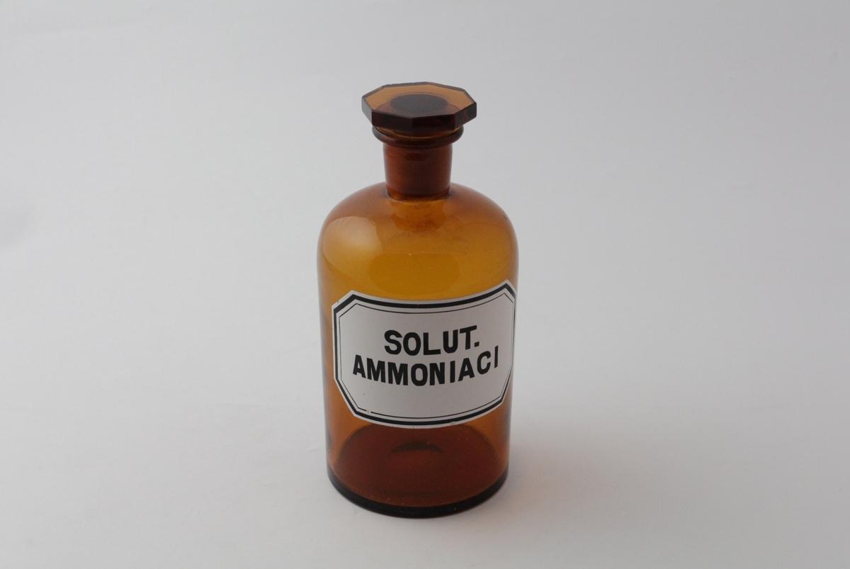 Brun glassflaske med smal hals og slipt glasspropp med åttekantet topp. Påført hvit etikett med sort skrift og sorte kantlinjer. Flasken har blitt brukt til oppbevaring av ammoniakkløsning (salmiakkløsning) som ble brukt i legemiddelproduksjon på apotek.