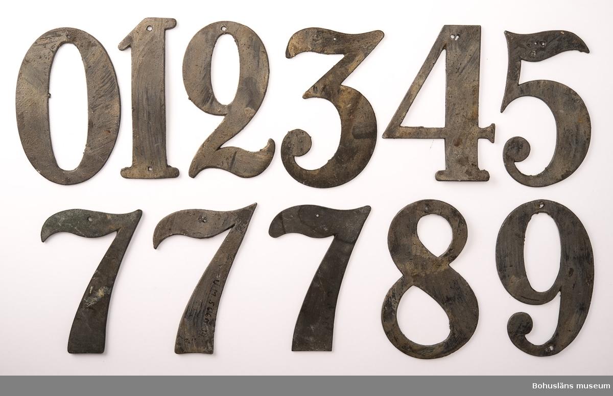11 psalmnummersiffror av bly och mässing, höjd 10 cm.  0, 1, 2, 3, 4, 5, 7, 7, 7, 8, 9. UM005660:032-042.  Ur handskrivna katalogen 1957-1958: Trälåda m. siffror för psalmnummer 1-8: Bly. H.: 16 cm, m. utsirningar 9-19: Bly. H.: 9 à 10 cm; m. utsirningar. 20-28: Bly o mässing. H.: 15 cm. 29-31 Bly H.: 13 cm. 32-42: Bly o mässing. H.: 10 cm. 43-51: Bly o mässing. H.: 7 cm. 52-54: Gjutna av gulmetall. H.: 10 cm. 55-56: Vitmålad järnplåt. 57: Bly. H.: 10,5 cm.  Lappkatalog: 13