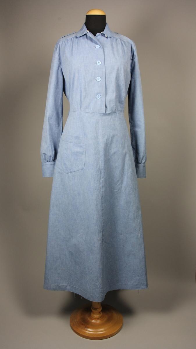 Blå långärmad klänning med 4 knappar till midjesömmen mitt fram. Framstycket är rynkat mot ett litet ok fram och har två veck vid midjan. På klänningens insida i halsringningen finns små vita knappar för att fästa en löskrage. Klänningen har hällor för ett skärp som inte finns kvar. på högersida finns det en ficka på kjolen. Bakstycke och bakre kjoldel är i ett, men midjan markeras med en dragsko med resår.