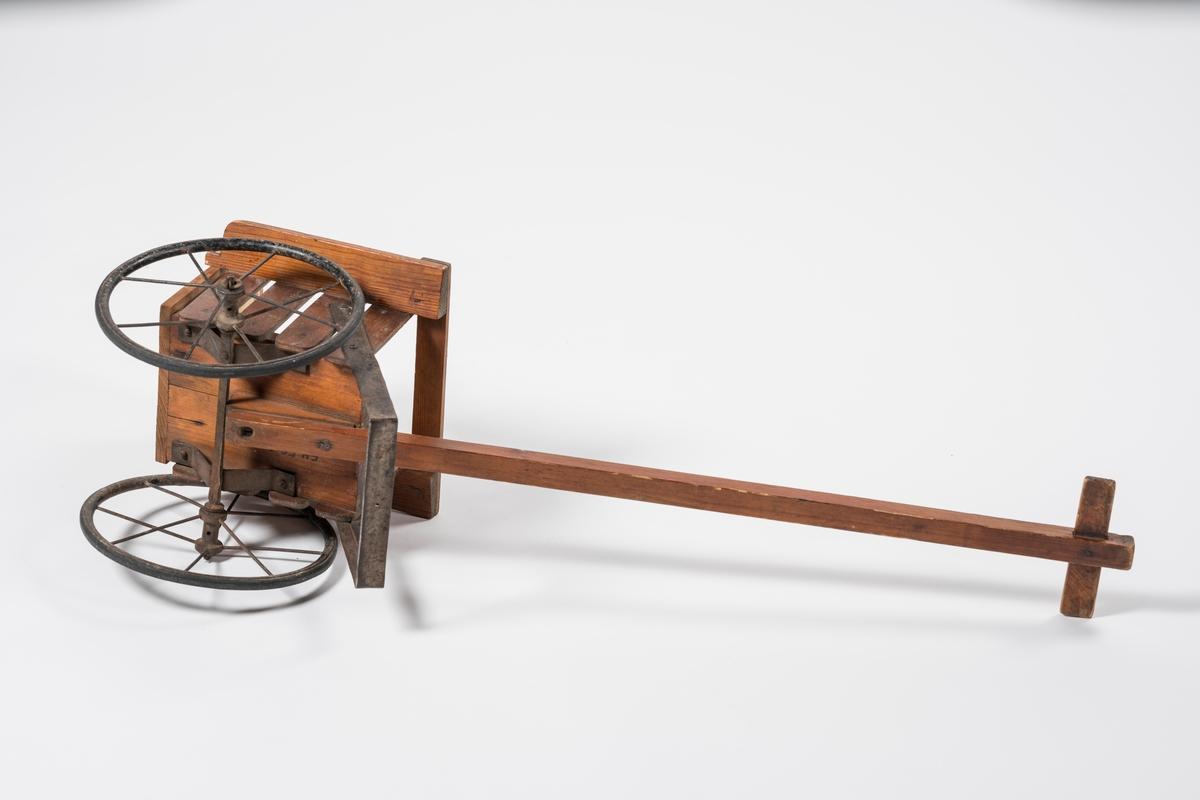 Teknikk: Saget, høvlet, smidd. Tredelene er festet til hverandre med jernstifter. Drastokken skrudd fast til understellet. Filten er festet med messingstifter. Lakkert. Form: Fating med rygg og armlener. 2 eikehjul. Støtte foran på fatingen. Drastokk med tverrtre.