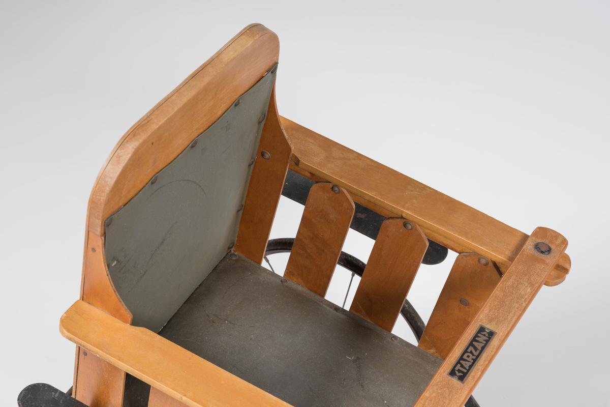 Fating utformet som barnesete med rygg, sidekanter, tverrstykke i forkant og fothvilere. Vinkelen på fothvilerne kan reguleres. Montert på aksling med to hjul. To mindre hjul i bakkant. Lang trekkstang med et lite tverrstykke ytterst. Både rygg og sete har stopp med lerretstrekk.