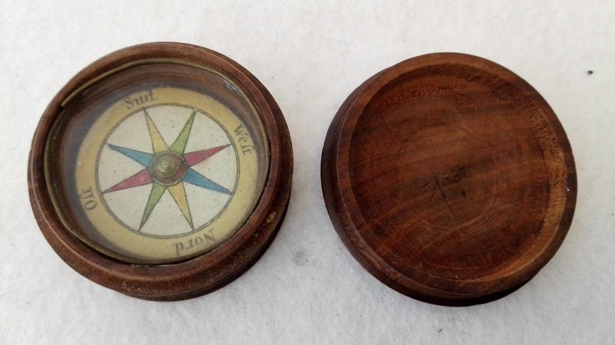 Kompas.  Kompas i liten dreiet trææske med laag. Over kompasset glas. Indre diameter 3,2 cm. Har tilhørt eidsvoldsmanden, generaladjutant O.E. Holck.  Gave fra datteren fru kaptein Hartvig, Alværen, Lavik.