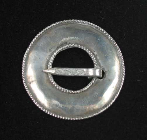 Bursprette med bred. svakt buet ring, som er kantet med pålagte tvinnetrådsbånd ytterst og rundt tornhullet. Tornen har en skravert sikksakkmønster og utenpå dette v-formet strekdekor.
