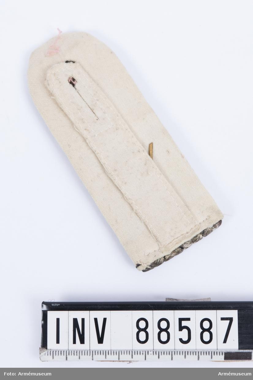 """En axelklaff med fyra vävda snören av silvertråd med svarta inslag (preussens färger) och nummer """"34"""" i mässing. Kantningen är av vitt kläde. Axelklaffen användes till den fredstida uniformen."""