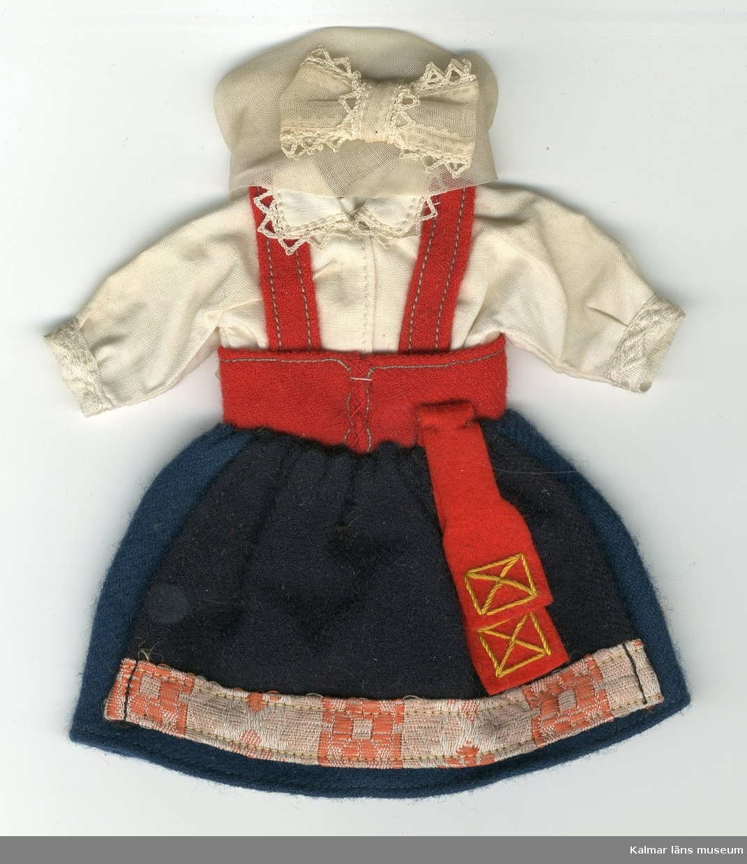 KLM 28082:70. Dockdräkt, dam, av textil, ylle och bomull. Dräkten består av kjol, förkläde, handkläde (?), väst, skjorta och huvudbonad. Nationaldräkt från: Värend (?) i Småland.