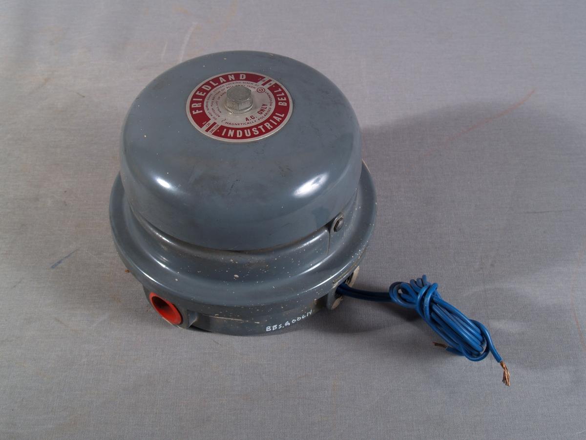 Vegghengt alarmklokke  for varsling av mannskap på hovedbrannsatsjonen ved brannalarm. Klokken går på vekselstrøm og har kabel fra basen. Varselklokken er sirkelrund.