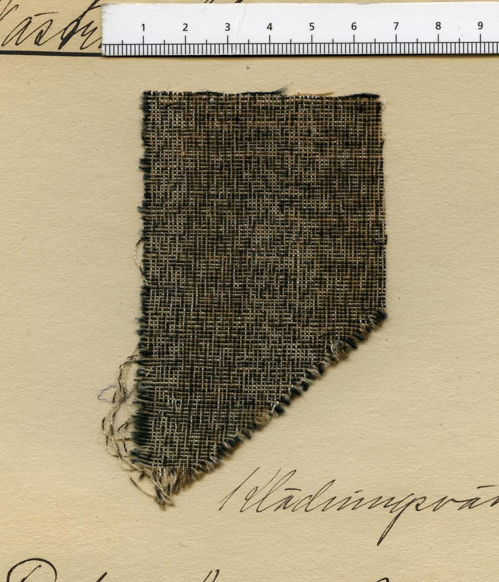 Anmärkningar: Vävnadsprov Olga Anderzons samling. Klänningsväv, Fröken Agnes Olsson, Näs Skedvi Västra Skedvi sn. Vävprov av halvylle i tuskaft, spräckligt. Bomullsvarpen är i vitt, brunt och beigt. Inslaget av ull är svart. L. 970 670 Br. 580 550