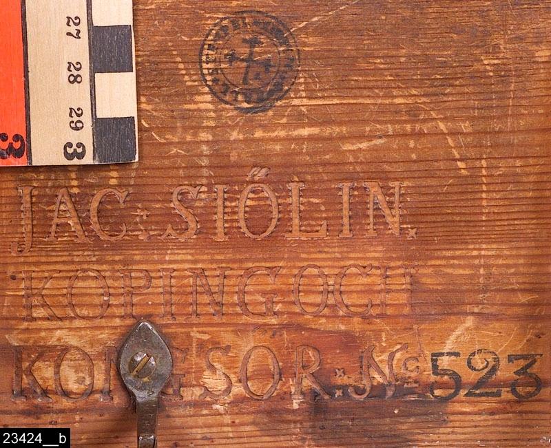 """Anmärkningar: Fällbord, Jacob Sjölin, 1780-1788.  Rund bordsskiva. Profilsvarvat ben. Tre S-formade fötter. Baktill finns stämplar som lyder """"KÖPINGS HALLSTÄMPEL"""" samt """"JAC. SIÖLIN. / KÖPING OCH / KONGSÖR: No 523."""" (bild 23424__b). Baktill finns också en anordning i järn som gör att bordet går att fälla upp samt ställa i låsbart läge då det är nedfällt (bild 23424__c) H:925 Diam:405  Bordet går att fälla upp, höjden blir då 925 mm. I nedfällt tillstånd är det 700 mm högt (bild 23424__d). Bordsskivan är fanerad med alrot, blindträet är furu. Alroten är fernissad. Benet och fötterna är av ljust lövträ och är också svärtade. Bild 23424__e visar närbild på bordsskivan.  Mälardalen och framför allt städerna Arboga, Köping, Kungsör och Eskilstuna var under 1700-talets senare hälft och början av 1800-talet centrum för tillverkning av alrotsfanerade möbler och föremål. Här tillverkades bl.a. fällbord, byråar och olika sorters askar. Föremålen såldes inte bara inom mälardalen utan även till Stockholm och till andra länder. Det främsta namnet inom alrotsföremålsproduktionen är Jacob Sjölin (1737-1785). Alroten togs inte från alens rötter utan från stamansvällningar vid rötterna. I synnerhet vid Mälarens stränder har tillgången på detta sorts virke varit god. På slottet förvaras en kortkatalog, upprättad av f.d. antikvarie Carin Thorsén. Den upptar över 300 alrotsföremål tillhörande museer, privatpersoner etc.  Jacob Sjölin (1737-1785), gick i lära hos Jonas Nordling i Arboga. Sjölin blev mästare under hallrätten i Köping och Kungsör 1767 och kvarstod som mästare intill sin död 1785. Ungefär 2000 föremål tillverkades i hans verkstad. Sjölins speciella ytbehandling (fernissa) på möblerna gav dem en särskild glans och hållfasthet. Ingen mästare i Sverige har överträffat Sjölin i framställandet av alrotsfanerade möbler. Sjölin använde sig av tre olika brännstämplar, av Åke Nisbeth klassificerade som typ A, vilken är äldst men också använd under hela Sjölins livstid och även efter"""