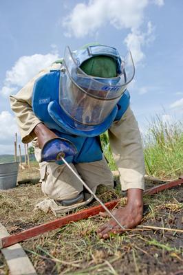 Minerydder i aksjon, med verktøy, blå vest og hjelm med visir.