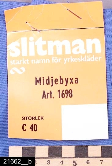 Anmärkningar: Byxa för damer, 1983.  Långbyxa, dammodell av blått tyg 65% polyester, 35% bomull. Modellen har snedfickor fram med knäppning i anslutning till fickorna, knappar av plast. Storl 40, art 0618. Tryck i gult på ena fickpåsen. Enköpings kemtvätt.  Tillstånd: Nyskick.  Historik: Inköpt från Gränges aluminium, Skultuna, i samband med samtidsdokumentationen där 1983 för 65 kronor+ moms. Byxan användes av kvinnlig personal på folieförädlingen samt på Skultuna messingsbruk. Byxan är tillverkad av Slitmanfabriken AB, Sala.