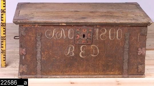 """Anmärkningar: Brudkista, målad datering 1800.  Gångjärnsförsett platt lock med rödmålade järnbeslag i hörnen. Kortsidorna är försedda med järnhandtag. På framsidan finns de målade påskrifterna """"ANO 1800"""" samt monogrammet (BED). Mellan påskrifterna sitter en stor nyckelskylt av järn med hjärtformade dekorer (bild 22586__b). Även beslagen på framsidan är hjärtformade liksom de tolv hörnbeslagen runtom kistan. Invändigt finns en läddika till vänster (bild 22586__c). På insidan av locket finns ett blomstermåleri samt den målade påskriften """"Lars Anders Son I Nårby / Brita Ers Doter I Nårby / ? och kumla by eger denna kista"""" (bild 22586__d). Utvändigt är hela kistan brunmålad och bär spår av naturligt slitage. H:410 L:945 Dj:615  Tillstånd: Lås och nyckel saknas. Ett beslag på baksidan är skadat. Ett beslag på locket saknas."""