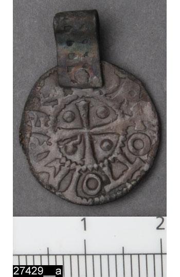 Anmärkningar: Badelunda sn, Tuna undersökt 1952-1953 Hänge, daterat till vikingatid, lösfynd från gravfält daterat till järnålder (ca 300-1050 e.Kr).  Hänge av silver. 1 st, av mynt som är omgjort till hänge med ögla.  Präglat i Köln för Otto I/II (962-983), (Bestämning gjord av Elsa Lindberger) Öglan av silverband är ornerad med två rader av punkter. Funnet i schaktmassor vid trappan. Diam 18,5 mm  (Myntet identiskt med mynt funnet i brandgrav 37 (invnr 28200)  Litteratur Nylén, E. & Schönbäck, B. 1994. Tuna i Badelunda. Guld kvinnor båtar II. Västerås kulturnämnds skriftserie 30. Västerås. s 191