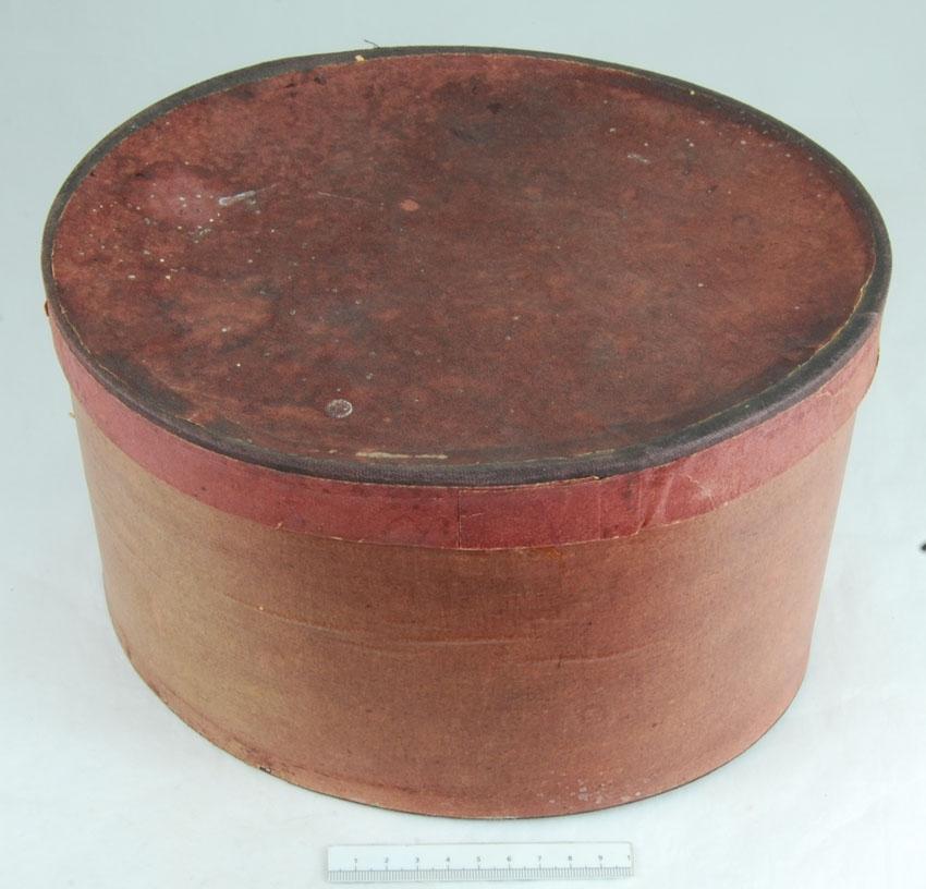 Anmärkningar: Irsta sn Geddeholm  Bindmössa, 1 st, av mörkblått siden med rosett bak. Inuti klädd med vitt siden. Mössan försedd med stycke framtill av naturfärgad spets. Tillhör folkdräkt. Förvaras i hög oval brun låda med lock. (Bindmössa, liten, styvad, rundkullig mössa, vanligen sidenklädd och broderad och ofta prydd med rosett baktill eller runt kullen. Den bärs högt uppe på kvinnans huvud och kompletteras av ett stärkt, spetsprytt s.k. stycke av lin. Källa NE)