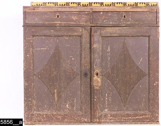 Anmärkningar: Skänk, brunmålad, omkring 1800.  Två draglådor. Spegelförsedda pardörrar med gerade och profilerade lister. Speglarna är försedda med fyrkantiga räfflade fyllningar. Nyckelskylt på vänster dörr. Invändigt tre hyllplan (ett mindre och två större). På insidan av höger dörr sitter ett lås i järn, tillhörande nyckel i järn (bild 5856__b) och på insidan av vänster dörr sitter en hank i järn, tillhörande hankfäste finns på nedersta hyllplanet. H:1045 Br:1190 Dj:450  Tillstånd: Överst saknas lister. Nyckelskyltar saknas på båda draglådor samt på höger dörr. Låset är senare. Färgen är sliten på hela skänken. Lösa delar ligger i höger draglåda (bild 5856__b).  Historik: Inköpt å auktion på Ålderdomshemmet, av K. Lundevall, Västerås.  Negativnummer X-1695