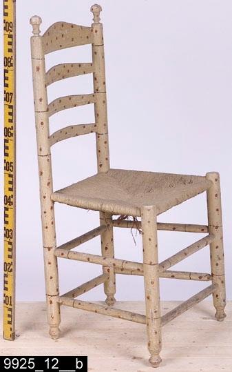 Anmärkningar: Stegstol, 1700-talets mitt eller senare hälft.  Överstycke med vågformad överkant och profilerad nederkant. Runda bakstolpar med svarvade dekorer längst upp. Genombruten rygg med tre ryggslåar som ser likadana ut som överstycket. Sits av flätad halm. Fyra runda ben med profilsvarvade fotavslutningar (bild 9925_12__b). Åtta benslåar förbinder benen. H:960 Br:490 Dj:415  Hela stolen är målad för att imitera bambu. Möblerna i serien 9925:1-12 söker imitera bambu. Sådana möbler har i omgångar varit populära i Sverige alltsedan kinasvärmeriet från mitten av 1700-talet till sekelskiftet 1800/1900. Enligt litteraturen på området tillverkades möblerna ofta för lusthus, en uppgift som också stöds av proveniensen från museets möbler - de har enligt liggaren stått i ett lusthus på herrgården Gideonsberg (riven på 1950-talet)!  Stegstolarna med invnr. 9925:7-12 (samt invnr. 28525) är inte tillverkade av Ephraim Ståhl. De är något äldre, förmodligen är de tillverkade runt 1700-talets mitt eller senast vid slutet av 1700-talet - åtminstone innan Ståhl blev mästare. Stegstolarna har målats samtidigt som, de av Ståhl tillverkade stolarna, d.v.s. omkring 1800. Stegstolarna har dock två lager av underliggande grå färg i olika nyanser av grått (även sitsen har varit gråmålad) som skymtar fram på flera ställen (bild 9925_12__c, tydligast framgår detta på bild 9925_10__c), vilket möblerna av Ståhl saknar. Troligen har den ursprunglige beställaren velat komplettera uppsättningen av Ståhlmöblerna och då tagit stolar som redan funnits på gården och låtit måla dem i samma stil som Ståhlmöblerna. Det råder ingen tvekan om att det bambuimiterande måleriet på stegstolarna och Ståhlmöblerna är utfört av två olika målare. För det första är måleriet mer klumpigt utfört på stegstolarna (vilket i sig pekar mot att en lokal gårds/bymålare utfört måleriet) än måleriet på Ståhlmöblerna som kännetecknas av tunnare och finare linjer. För det andra skiljer blandningen av färgen möblerna åt.
