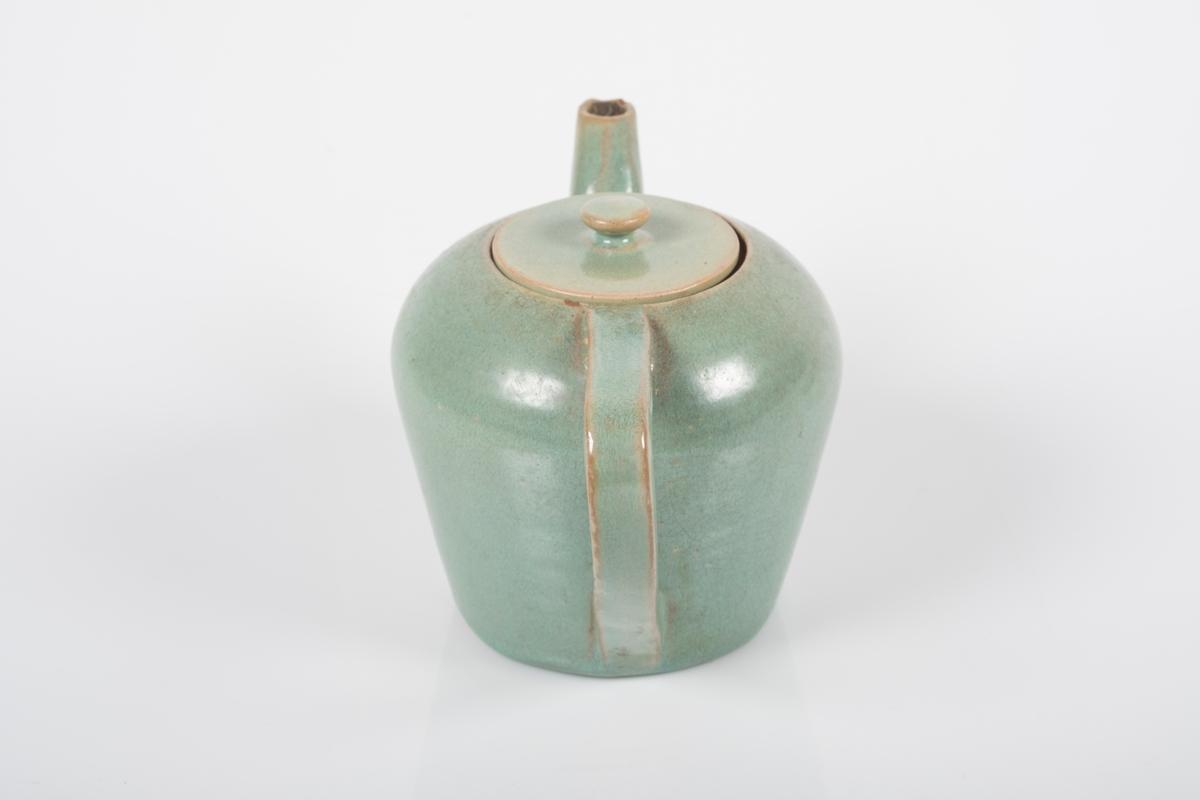 Tekanne i keramikk med grønn lasur.  Består av to deler; kanne og lokk. Kannen har tut og buet hank. Lokket har knott som håndtak. Grinisymbolet på bunnen av tekannen. Tre små knotter på undersiden av kannen, usikker funksjon.