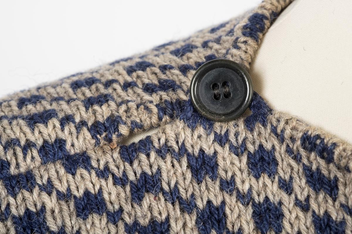 Blå og grå strikket herregenser.  To knapper ved halsåpningen for å kunne kneppe den igjen.  Ermekantene er brettet innover og sydd fast.  To sømkanter på baksiden av genseren.