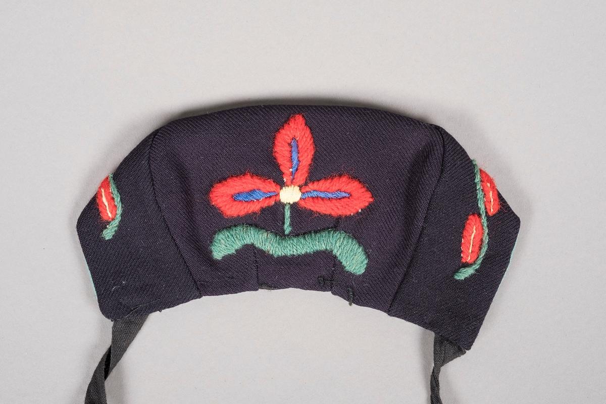 Mørkeblå kyse, med blomsterbroderier i blått, grønt, rødt og lysegult. Kysen er foret i blågrønt bomullsstoff og har en stor rød blomst bak på hodet.