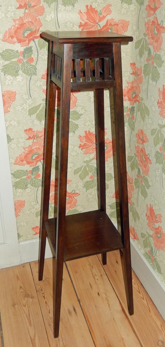 Piedestal, blomsterpiedestal, av obehandlad furu. Ursprungligen mörkt brunbetsad. Fyra ben, med kvadratisk genomskärning, något utställda. Plan ovansida för placering av blomma och under gallerverk på varje sida i form av fyra stavar. Hyllplan.