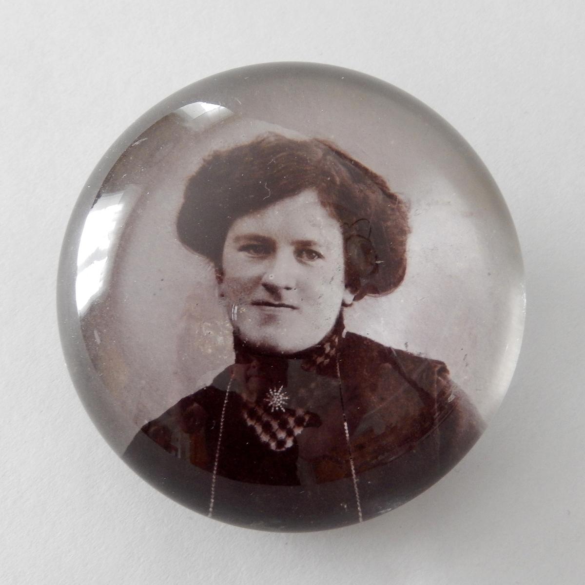 Brevpress av klart glas, halvsfärisk. I botten svartvitt fotografi föreställande kvinna, bröstbild med mörk klänning och mörkt uppsatt hår.