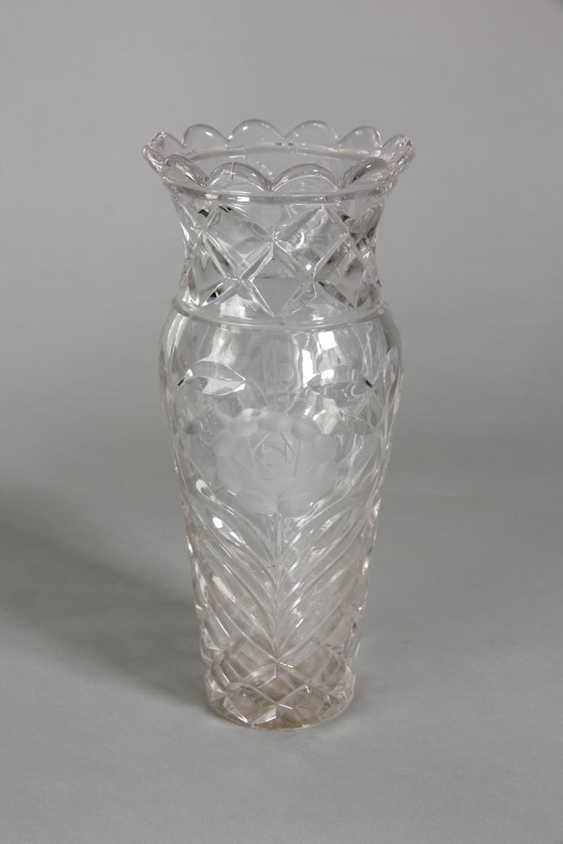 Vas av pressat klart glas med blom- och rutmönster. Något indragen hals. Mynningskanten avslutas med 12 bågar.