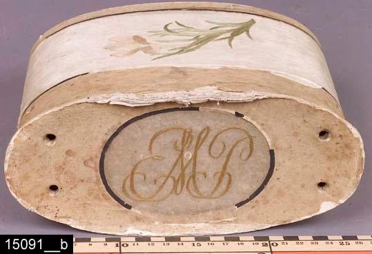 """Anmärkningar: Ask, 1800-tal.  Oval ask med lock. På locket finns de broderade initialerna """"EMP"""" samt fyra hål (för bärhandtag?)(bild 15091__b). På båda sidor finns vardera en broderad blomma. Hela asken är av papper och delvis klädd med siden, som underlag för broderierna. H:190 Br:235 Dj:105  Tillstånd: Små skador på pappret. Pappret har gulnat.  Historik: Gåva från fru Nanne Andersson, Utanbygatan 15, Västerås, 1968."""