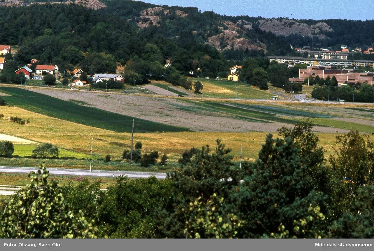 Del av Fässbergsdalen, Mölndal, i juli 1994. Vy från Balltorp mot Östra Fässberg och Prästgården. Till höger ses även Lärarhögskolan samt bostadsbebyggelse i Bifrotsområdet. FD 7:5.