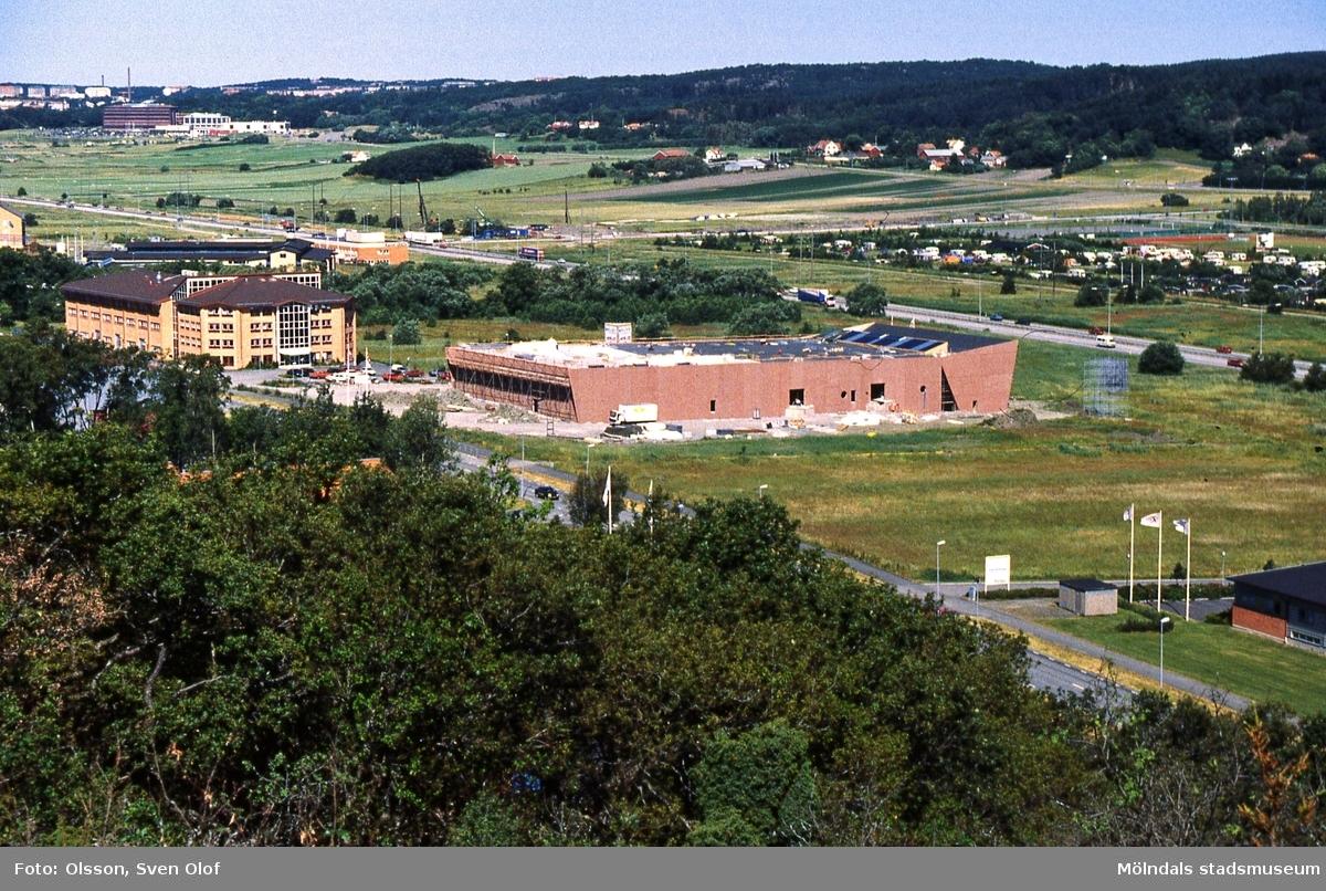 Del av Fässbergsdalen, Mölndal, i juni 1995. Industribyggnad under uppförande vid Aminogatan i Balltorp. Väster om detta hus ligger Bygg Götas kontorsbyggnad. I bakgrunden ses även bebyggelse i Eklanda och Fässberg.