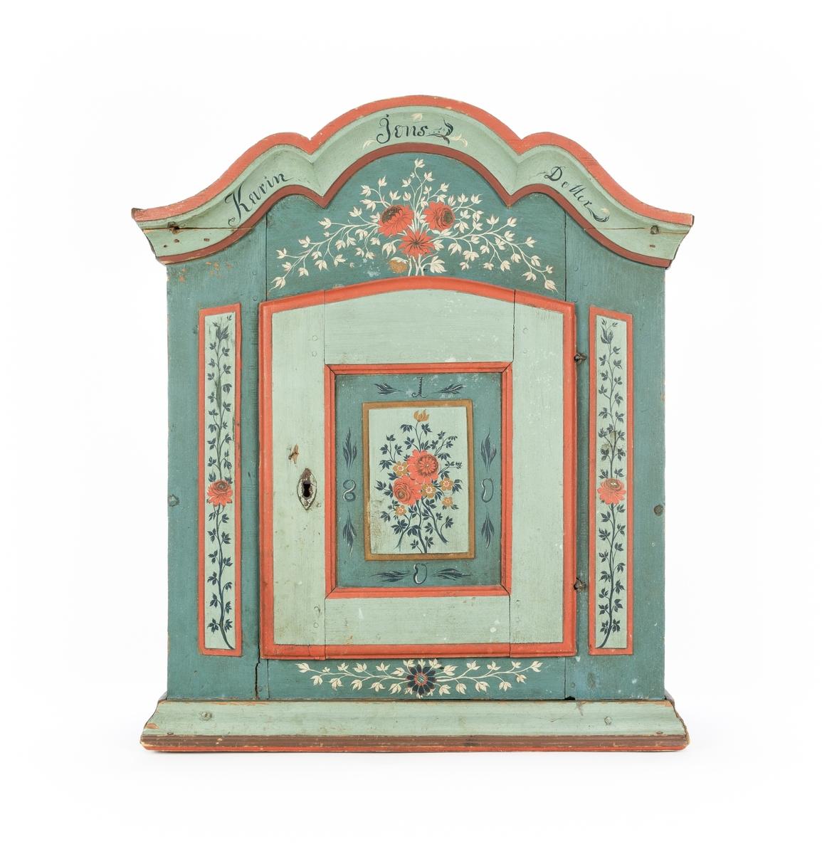 Hängskåp, med en dörr. Svängt överstycke. Målat i blå-grön färg med blomdekor i rött, vitt och brunt.