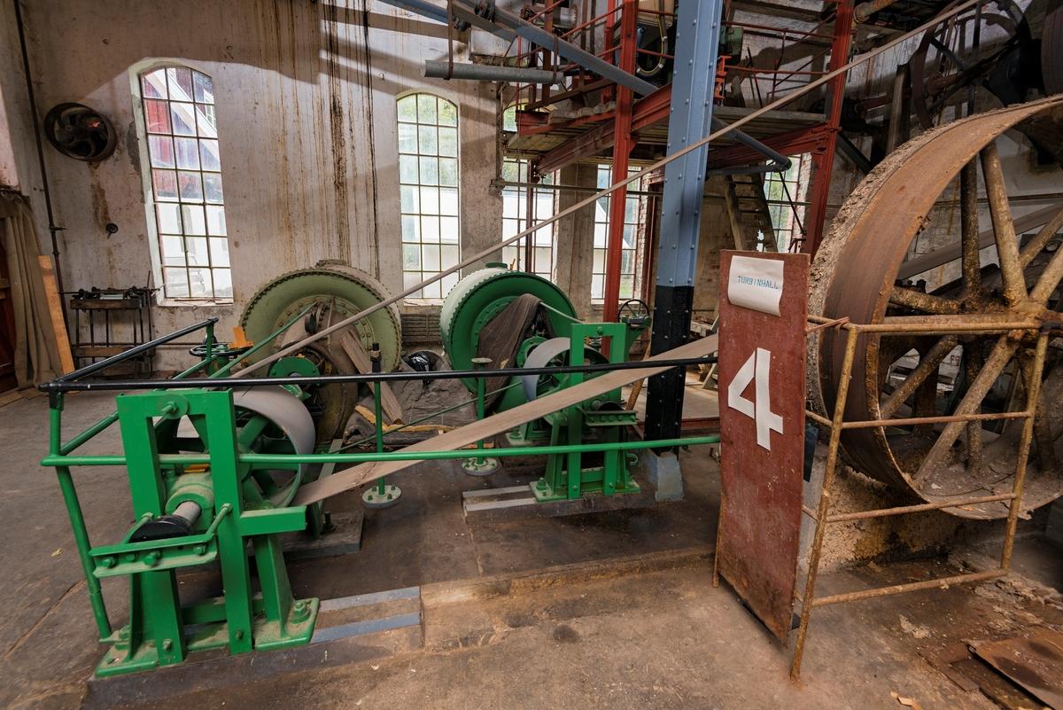 Interiør fra turbinhallen ved Klevfos industrimuseum på Ådalsbruk i Løten, Hedmark.  Dette fotografiet viser fabrikkens to frrancisturbinene og de kraftige balatareimene som overførte kraft til maskinene i fabrikken.  Hver av turbinene hadde en yteevne på cirka 80 effektive hestekrefter, men fordi vannføringa i Svartelva var ujevn, var det nødvendig å supplere med en kraftig elektromotor.  Plata (til høyre i forgrunnen) med 4-tall og en liten plakat som forteller hva man ser er montert etter at Klevfos Celulose- & Papirfabrik ble gjenåpnet for publikum som museum i 1986.  Det øvrige interiøret ble antakelig installert da fabrikken ble gjenoppbygd etter brann i perioden 1909-1911.