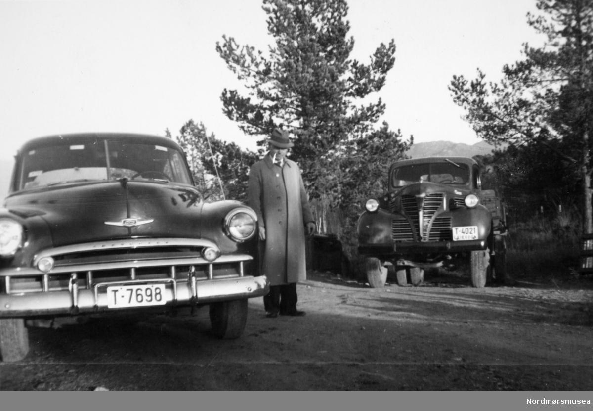 """Fra venstre Chevrolet 1949, Fargo 1939 lastebil. (Info fra Ivar Stav),  Fargo lastebilen er nok en 1946 modell. (mener Jo-Olav Bakken). --- en mann mellom to kjøretøy. Den ene en bil med skilt """"T-7698"""" mens den andre ser ut til å være en leievogn/lastebil med skilt """"T-4021"""". Det er usikkert hvor bildet er tatt, men trolig på Nordmøre i Møre og Romsdal. Fra Paulsen-samlingen, ved Nordmøre museums fotosamlinger."""