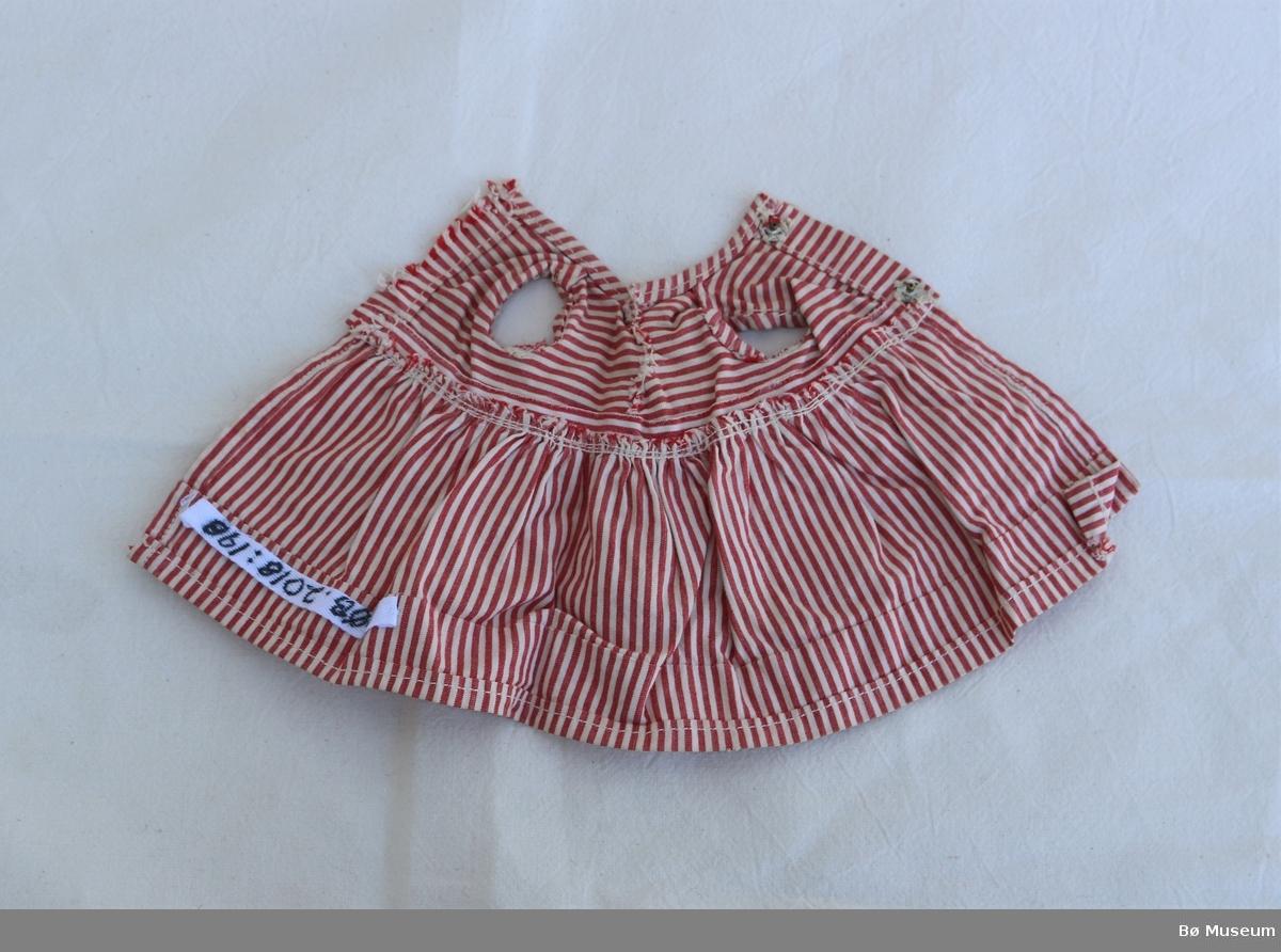 Stripete kjole til dokke. Den har to trykknappar i ryggen, men den øverste manglar den eine delen. Fronten er klypt eller rivd opp og sydd saman att. Erma er rulla inn og sydd fast. Den har ei rysje nede på skjørtet. Skjørtet er sydd til overdelen med rynker. På overdelen går stripene horisontalt, på underdelen vertikalt, og i halsen på skrå.