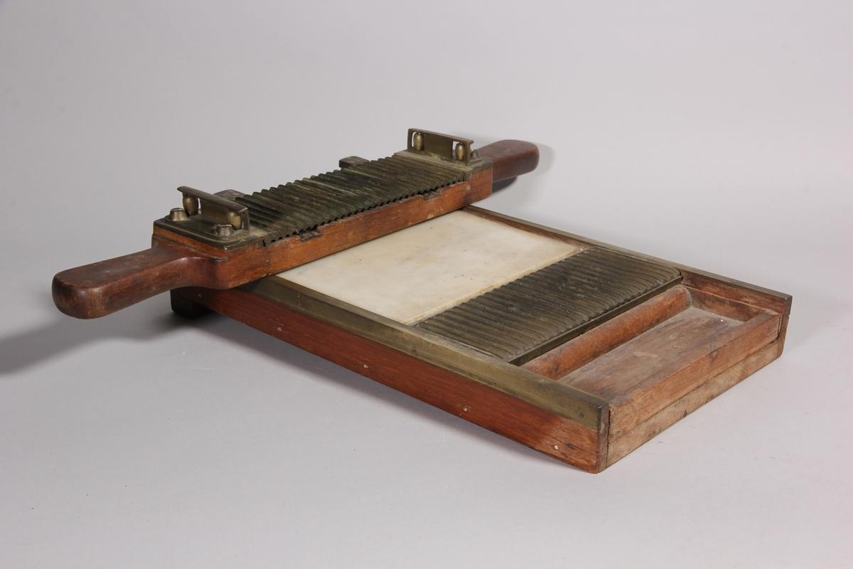 Pillermaskin av trä. Rektangulär låg låda med invändig marmorplatta samt längsgående refflor av metall och gradering. Lådan skodd med mässing. Lös del av trä med handtag och refflad metallundersida. Den lösa delen med refflorna dras över motsvarande del i lådan.