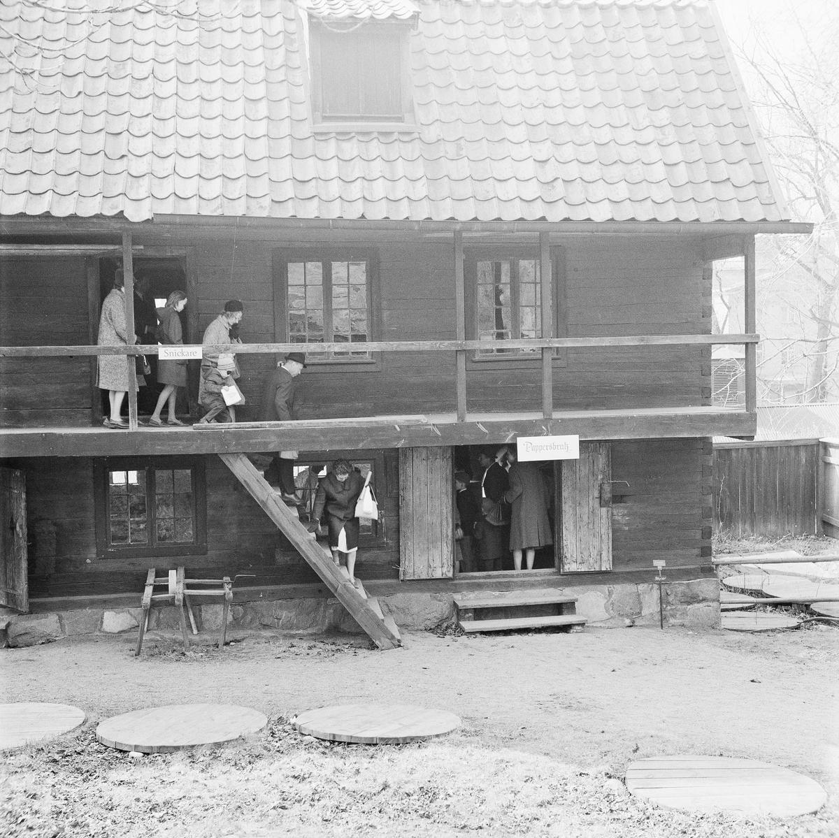 """Garverigården på Skansen. Besökare. Skyltar """"Snickare"""" och """"Pappersbruk""""."""
