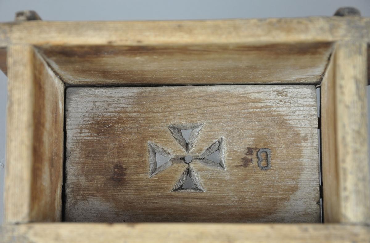 Osteform av tre, består av to sideplater, to endeplater og en bunnplate. Bunnplaten har et gjennomskåret georgskors i midten. Endeplater og sideplater holdes sammen av plugglåser, hvorpå det er satt inn plugger i alle fire hjørner. På utsiden av den ene endeplaten ser det ut til å være innrisset et bumerke.
