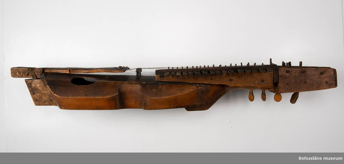 """Avlång, fiolliknande stråkinstrument med 19 s.k. nycklar med triangulär, skuren avslutning. Tre av stämskruvarna är större än de övriga och sticker ut på höger sida om halsen. De har dekorativt utskuret huvud. I skruvplattan är nio stycken mindre stämskruvar. Betsad. Högst upp på halsens undersida en ristad märkning i träet: """"16Y1"""" eller """"1671"""". Något defekt.  Stråken ser inte så gammal ut om man tittar på patina och slitage. Den är med största sannolikhet utförd vid senare tillfälle än själva instrumentet.  Om det är en kopia av originalstråken eller en fritt skapad form av en senare instrumentbyggare vet vi inget om och kommer heller aldrig att få veta.  Ur handskrivna katalogen 1957-1958: Nyckelharpa Renv.(?) L. 99. Relativt välbevarad. Med stråke.  Lappkatalog: 97 Inventerad 1957."""